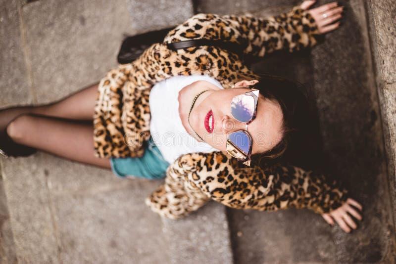 Портрет моды взгляда сверху молодой красивой уверенной женщины сидя и нося ультрамодное животное, меховая шыба faux печати леопар стоковые изображения rf