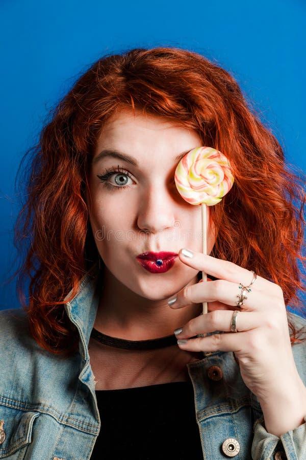 Портрет моды молодой красной женщины делая поцелуй воздуха с леденцом на палочке на красочной голубой предпосылке стоковое фото rf