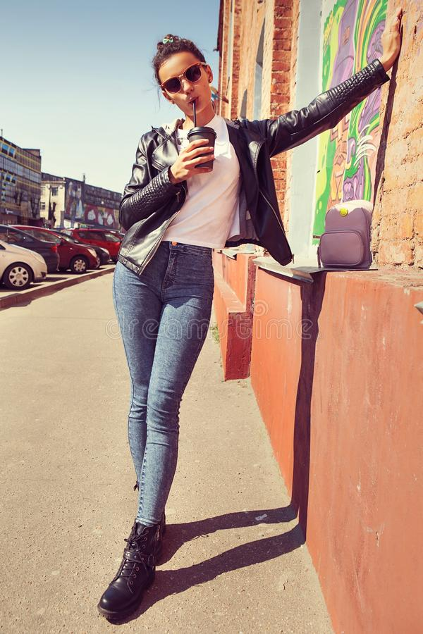 Портрет моды образа жизни лета солнечный молодой стильной женщины идя на улицу, нося милого ультрамодного обмундирования, выпивая стоковые фотографии rf