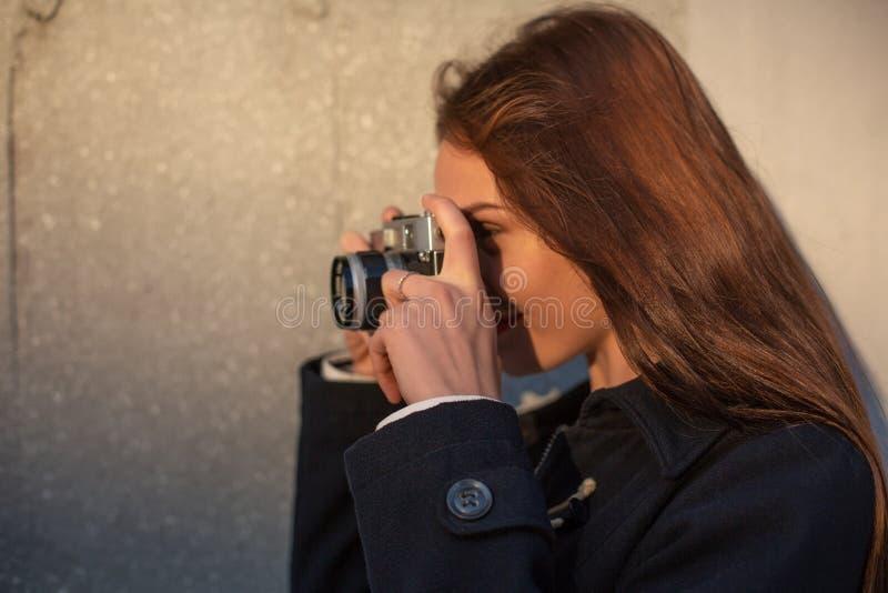 Портрет моды образа жизни солнечный молодой стильной женщины идя на улицу, с камерой, усмехаясь для того чтобы насладиться выходн стоковое фото rf