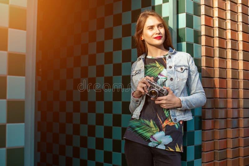 Портрет моды образа жизни солнечный молодой стильной женщины идя на улицу, с камерой, усмехаясь для того чтобы насладиться выходн стоковые изображения