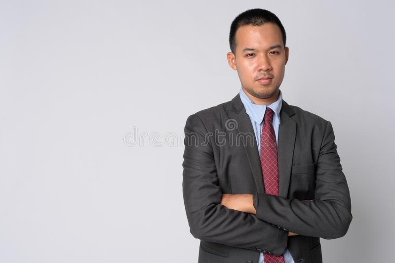 Портрет молодого азиатского бизнесмена в костюме с оружиями пересек стоковое фото rf