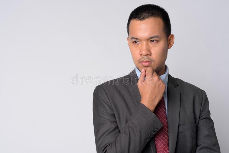 Портрет молодого азиатского бизнесмена в мысли костюма стоковое фото rf