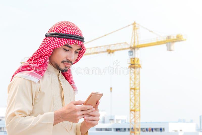 Портрет молодого аравийца держа смартфон и смотря к мобильному экрану на строительной площадке с предпосылкой крана стоковая фотография