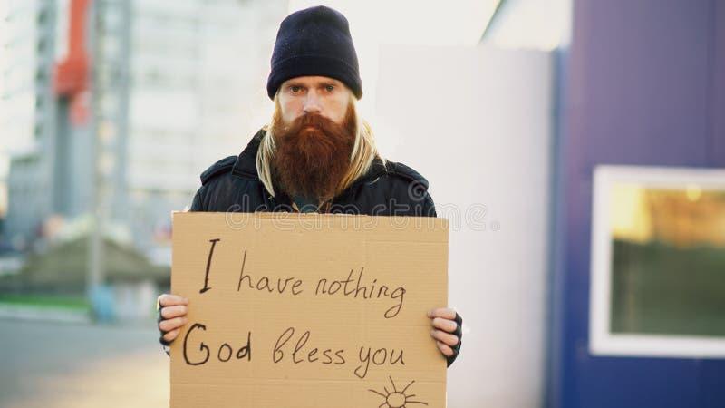 Портрет молодого бездомного человека с картоном поет положение на улице стоковые фото