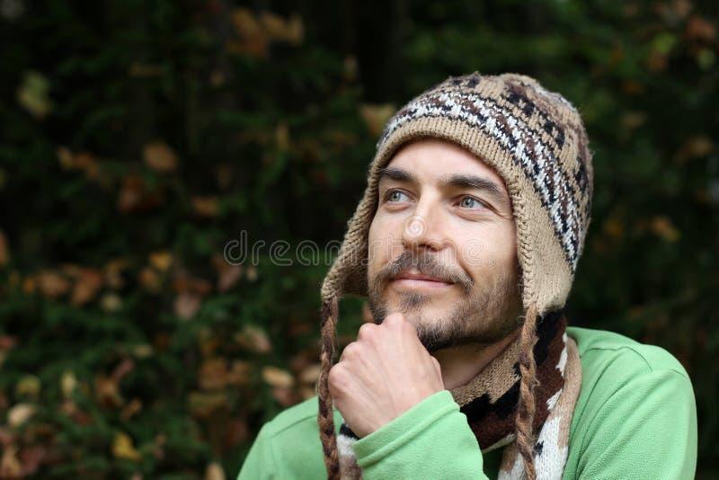 Портрет молодого бородатого усмехаясь человека в теплой шляпе на осени fo стоковое фото