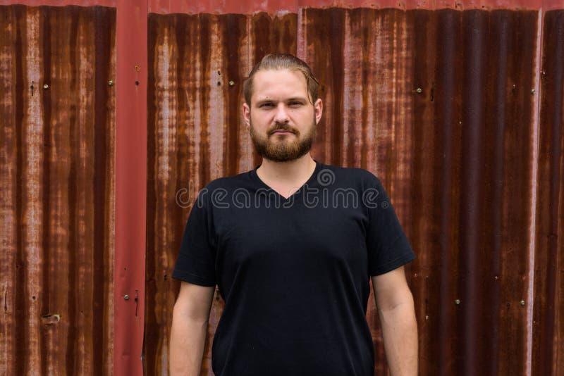 Портрет молодого бородатого человека с волосами связанными против старой ржавой стены листа стоковые фото