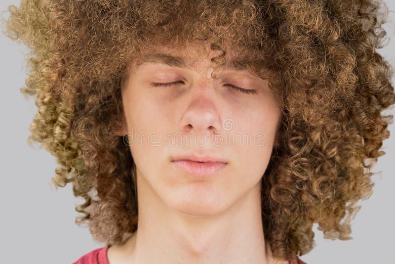 Портрет молодого вьющегося европейца с длинными вьющимися волосами и закрытыми глазами очень пышные мужские волосы кёрлинг стоковые изображения