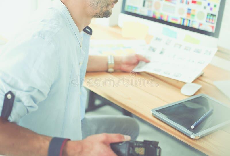 Портрет молодого дизайнера сидя на графической студии перед ноутбуком и компьютером пока работа онлайн стоковые изображения rf