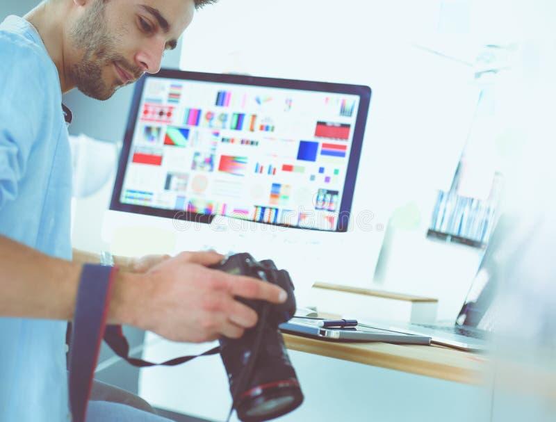 Портрет молодого дизайнера сидя на графической студии перед ноутбуком и компьютером пока работа онлайн стоковая фотография rf