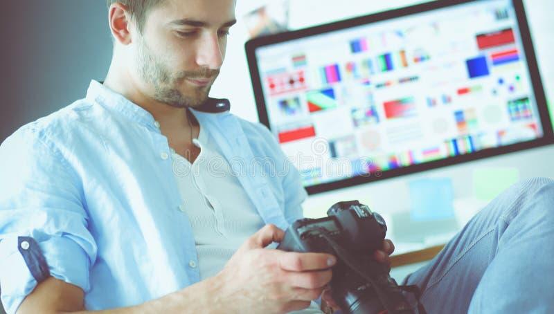 Портрет молодого дизайнера сидя на графической студии перед ноутбуком и компьютером пока работа онлайн стоковое изображение