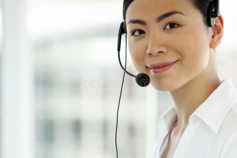 Портрет молодого женского азиатского оператора центра телефонного обслуживания стоковое изображение