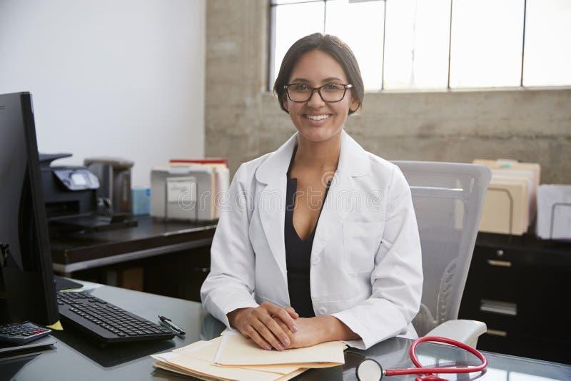 Портрет молодого женского доктора сидя на столе в офисе стоковое изображение