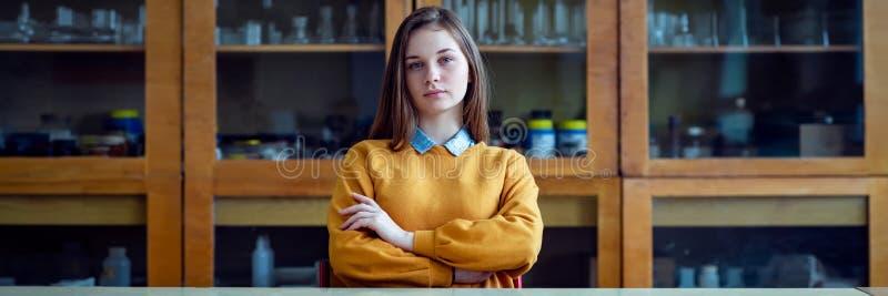 Портрет молодого женского студента колледжа в классе химии, сидя за столом с пересеченными оружиями стоковые изображения rf