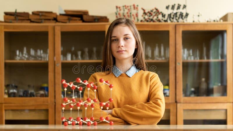 Портрет молодого женского студента колледжа в классе химии Сфокусированный студент в классе стоковые изображения