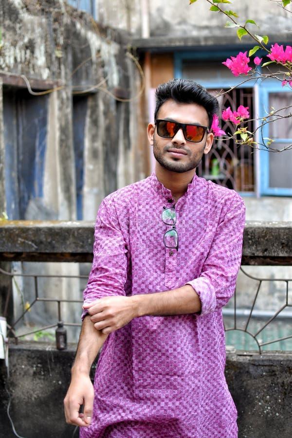 Портрет молодого и красивого индийского бенгальского положения человека перед винтажным домом нося зеленый индийский традиционный стоковые изображения