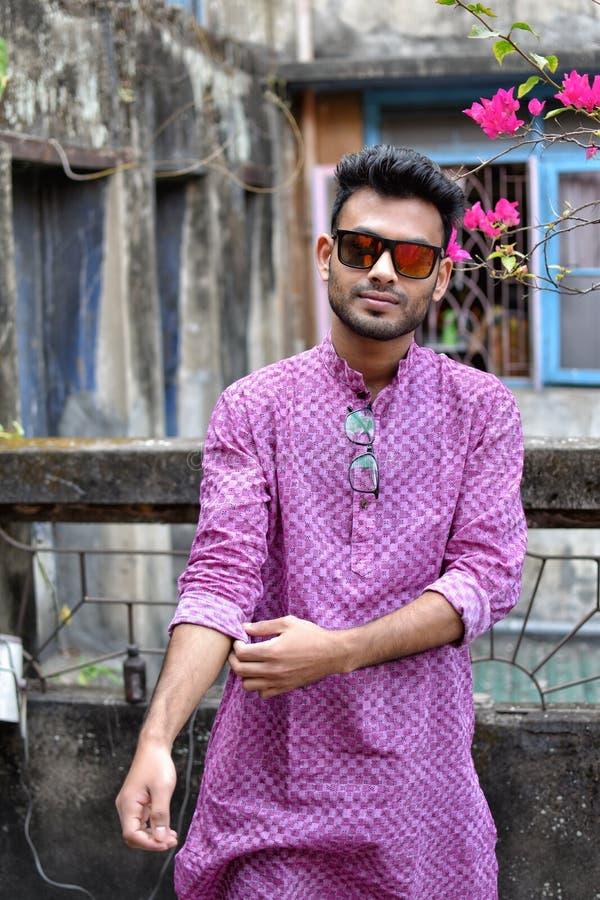 Портрет молодого и красивого индийского бенгальского положения человека перед винтажным домом нося зеленый индийский традиционный стоковые фото