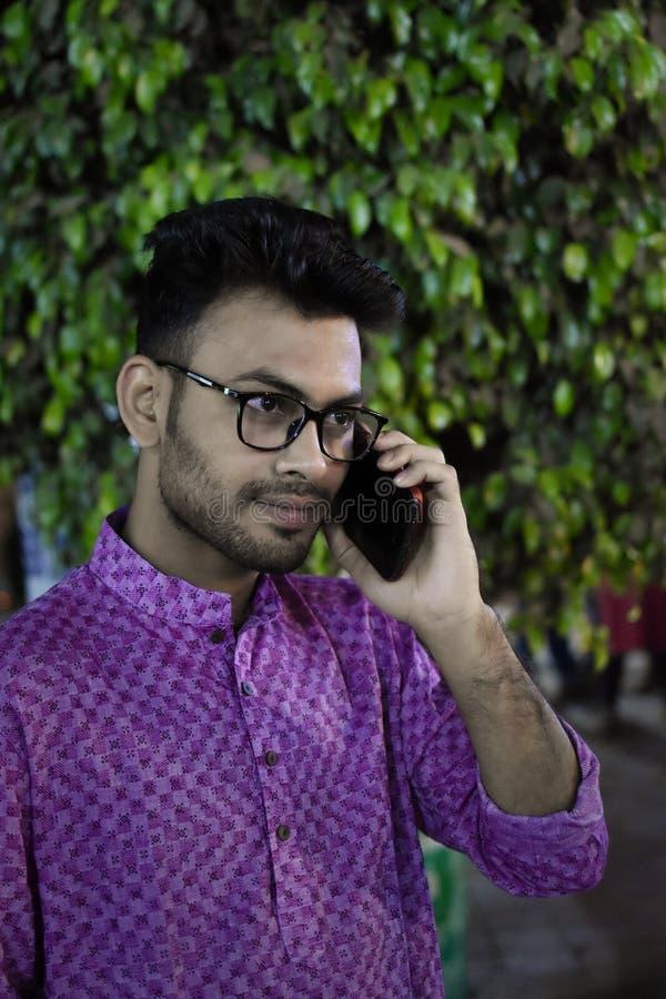 Портрет молодого и красивого индийского бенгальского положения человека перед винтажным домом нося зеленый индийский традиционный стоковое фото rf