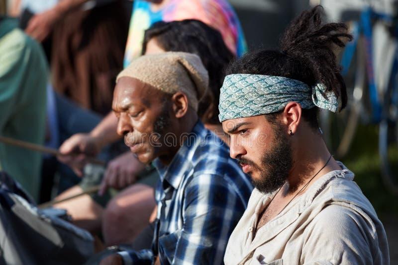 Портрет молодого красивого испанского латиноамериканца и и Афро-американского мужчины сидя в общественном месте стоковые изображения rf