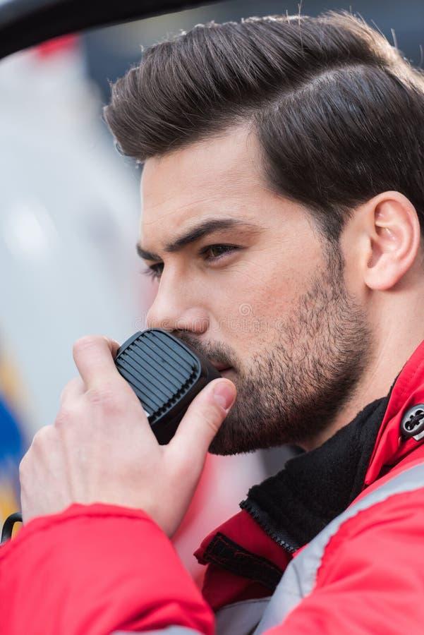 портрет молодого красивого мужского медсотрудника стоя близко машина скорой помощи и говорить стоковая фотография