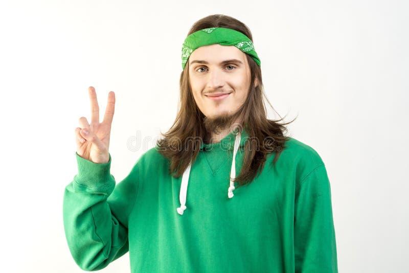 Портрет молодого красивого человека в зеленом hoodie с мирной улыбкой, смотря в камеру и показывая знак мира стоковое изображение