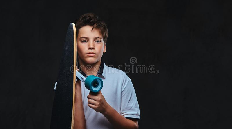 Портрет молодого мальчика конькобежца одел в владениях белых футболки longboard На темной предпосылке стоковая фотография