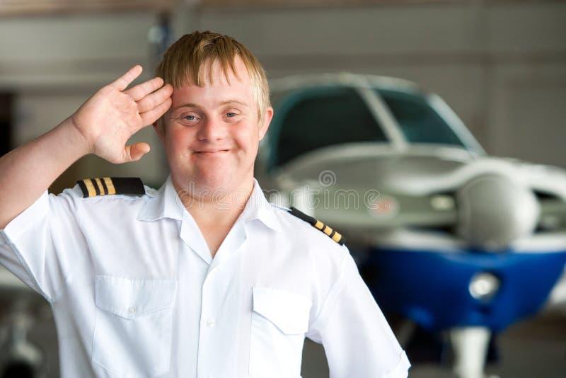 Портрет молодого пилота с Синдромом Дауна в ангаре. стоковое фото