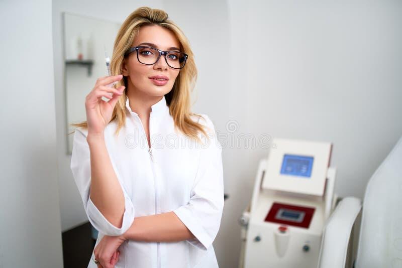 Портрет молодого привлекательного доктора beautician со шприцем в руке Cosmetologist держа медицинские инструменты Practician вну стоковые фото