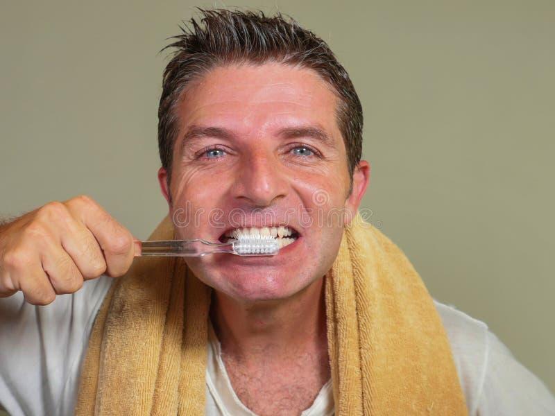 Портрет молодого привлекательного и счастливого кавказского bathroom человека дома моя его зуб с зубной щеткой смотря в зеркале в стоковая фотография