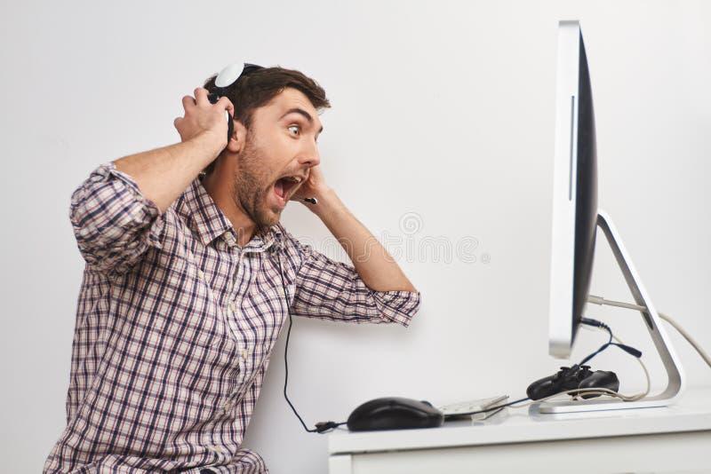 Портрет молодого смешного бородатого мужского gamer в checkered рубашке играя игры на персональном компьютере, нося наушники стоковое изображение