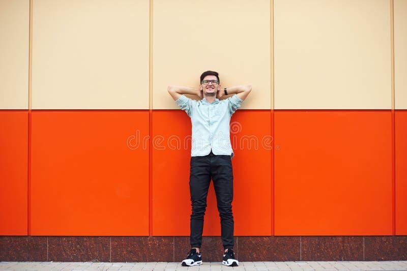 Портрет молодого счастливого человека ослабляя над оранжевой предпосылкой с его руками под головой стоковое изображение rf