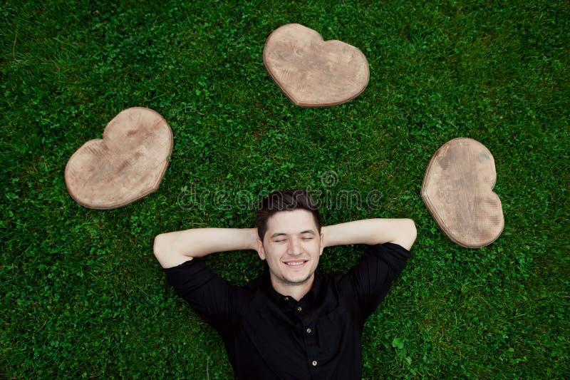 Портрет молодого счастливого человека ослабляя на траве с его руками под головой вокруг 3 сердца древесины стоковые фотографии rf