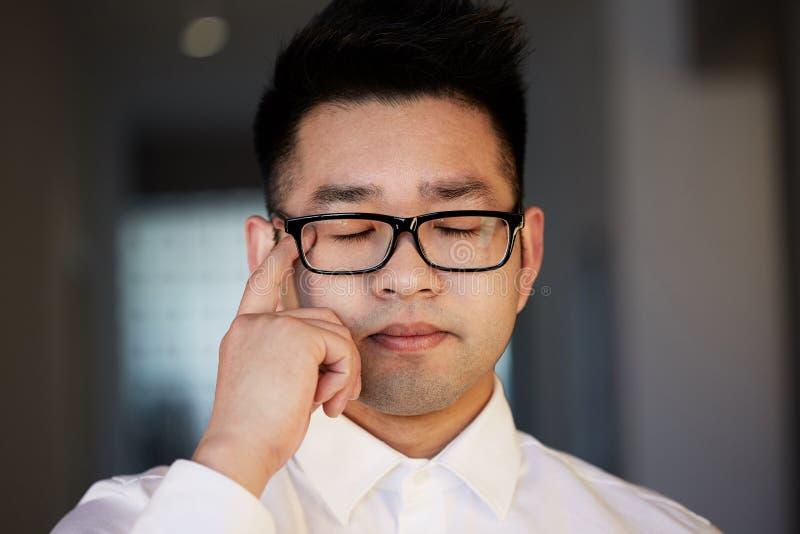 Портрет молодого уверенного азиатского бизнесмена думая на размерах офиса Соединяясь концепция сети стоковые изображения rf