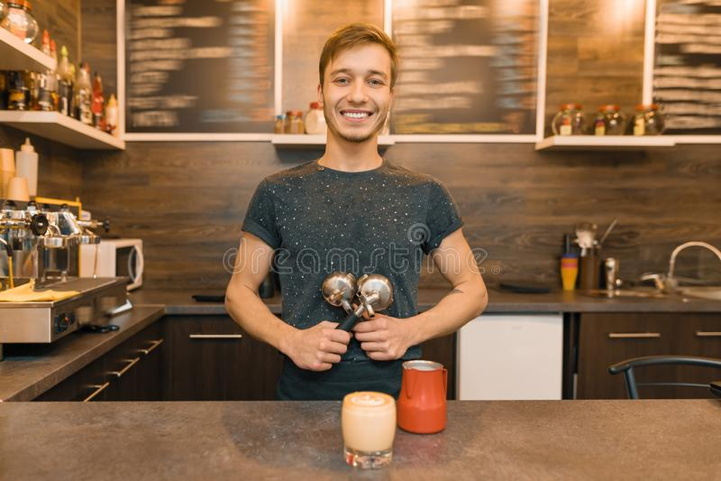 Портрет молодого усмехаясь мужского работника кафа, стоя на счетчике Человек со свежо сделанным кофе стоковая фотография