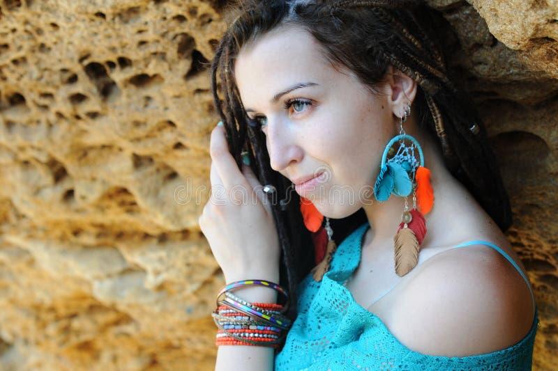Портрет молодого усмехаясь стиля причёсок dreadlocks женщины нося, одетый в голубом платье шнурка и голубых серьгах шика boho стоковая фотография
