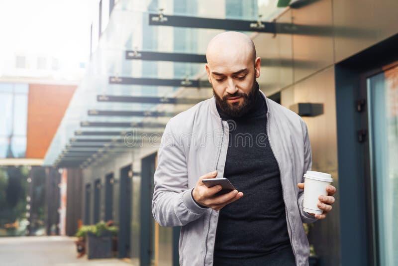 Портрет молодого усмехаясь человека используя смартфон на улице города Человек отправляет текстовое сообщение, выпивает кофе life стоковые изображения