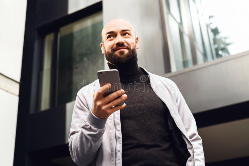 Портрет молодого усмехаясь человека используя смартфон на улице города Человек отправляет текстовое сообщение lifestyle Социальны стоковые фотографии rf