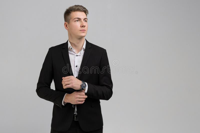 Портрет молодого человека в черном костюме выправляя рукав изолированный на белой предпосылке стоковое изображение rf