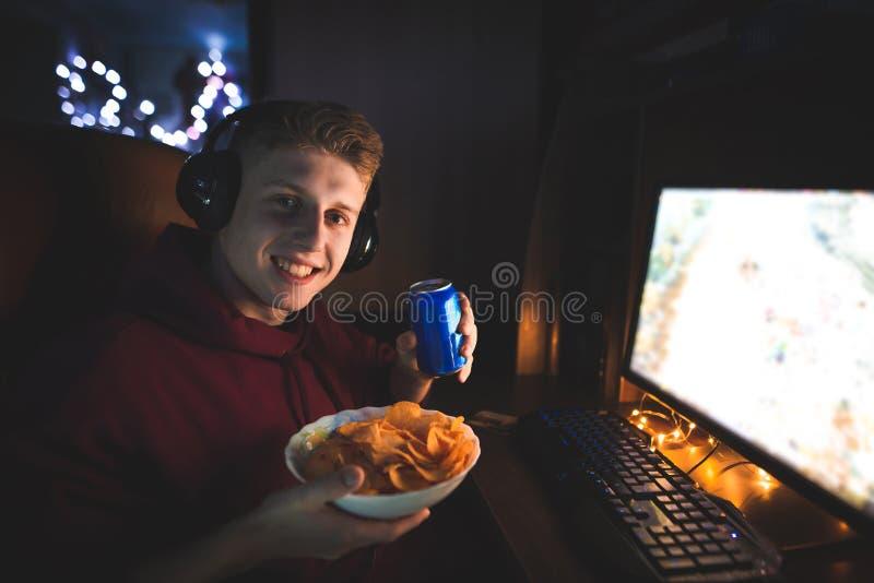 Портрет молодого человека играя gamer сидя в шлемофоне с консервной банкой колы в руках и плите стоковые изображения