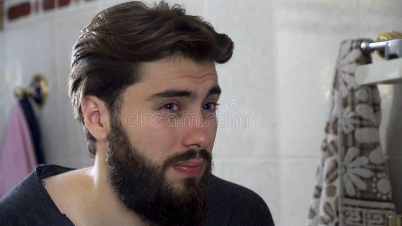 Портрет молодого человека подростка смотря себя в домашнем зеркале bathroom делая его волосы и получая готовый в стоковое фото rf