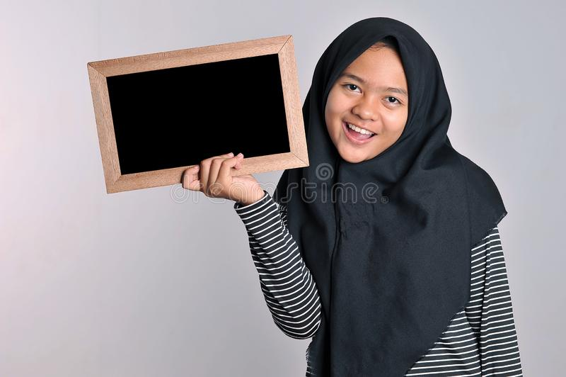 Портрет молодой азиатской женщины в исламской доске удерживания головного платка Усмехаясь азиатская женщина нося исламское удерж стоковое фото