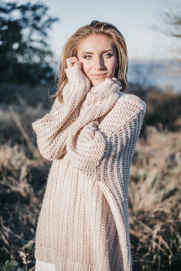 Портрет молодой белокурой девушки в теплом светлом свитере быть внешний стоковое изображение
