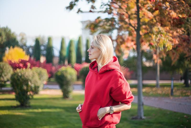 Портрет молодой белокурой женщины которая стоит в парке Она охлаждает вне стоковые фотографии rf