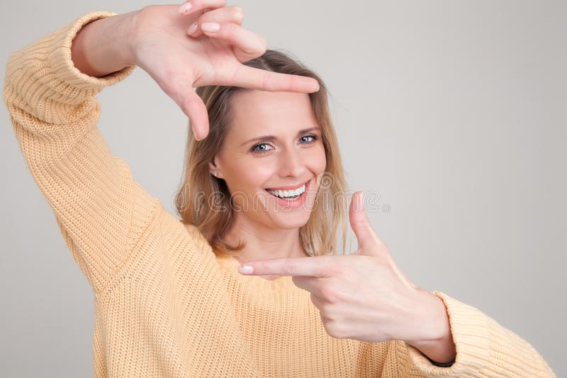 Портрет молодой белокурой женщины с жизнерадостным счастливым выражением на ее стороне, с хорошим настроением, делая квадрат с ее стоковые фотографии rf