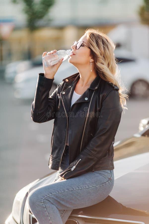Портрет молодой белокурой питьевой воды от бутылки сидя на клобуке черного автомобиля стоковое фото