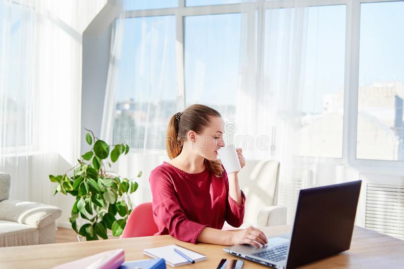 Портрет молодой бизнес-леди сидя на деревянном столе, выпивая кофе и работая на ноутбуке в современном офисе, космосе экземпляра стоковые фото