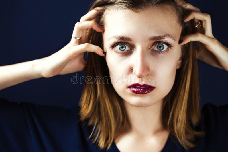 Портрет молодой взрослой белой женщины нося темную губную помаду сливы держа ее руки на сторонах ее руки наблюдает широко раскрыт стоковые фото