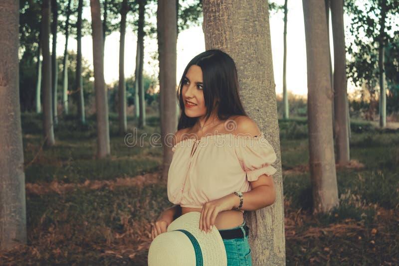 Портрет молодой девушки брюнета полагаясь на усмехаться дерева стоковое изображение rf
