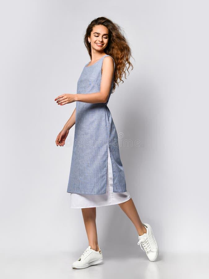 Портрет молодой женщины брюнета в голубом светлом платье представляя на светлой предпосылке, мода лета, подготавливая на дата стоковое фото