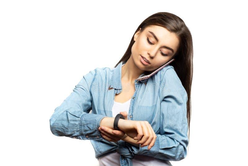 Портрет молодой женщины брюнет говоря на мобильном телефоне и смотря ее вахты стоковая фотография